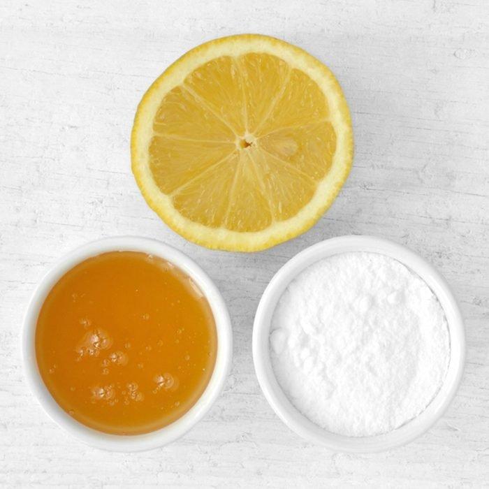 قناع للوجه مصنوع منزليًا من عصير الليمون والعسل وصودا الخبز على خلفية خشبية