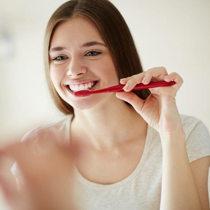 امرأة شابة تغسل أسنانها في المرآة