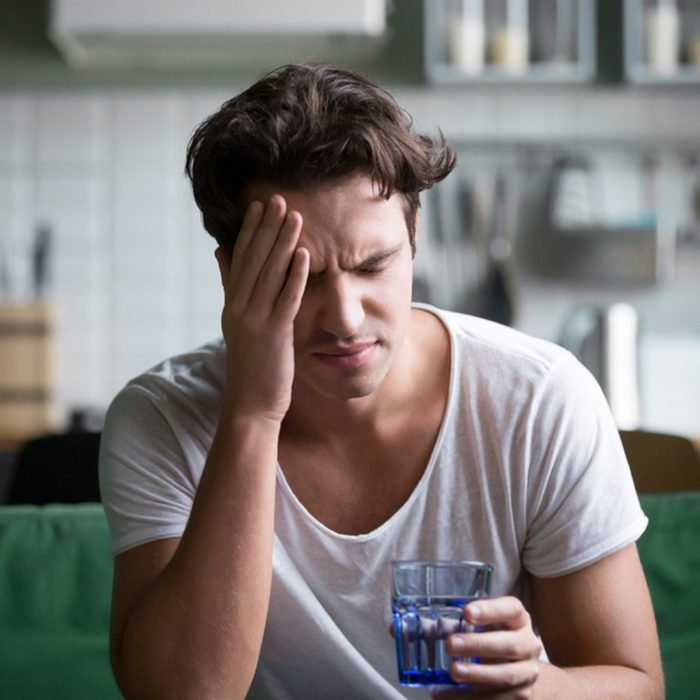 شاب يعاني من صداع شديد أو صداع نصفي يجلس مع كوب من الماء في المطبخ