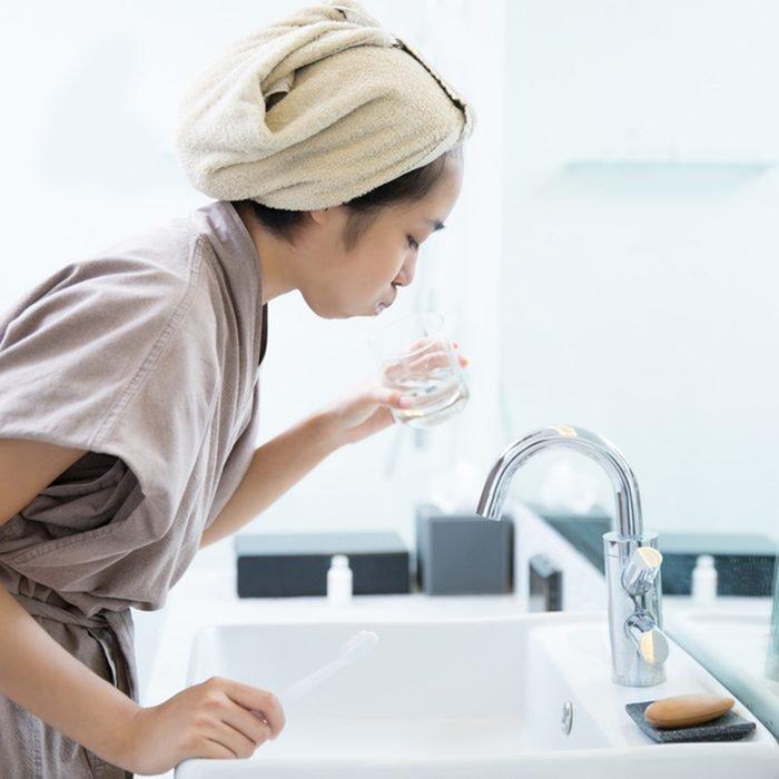النساء الآسيويات غسول للفم بعد تفريش الأسنان في الحمام.