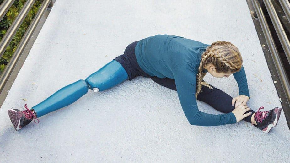 امرأة تجلس على الأرض وتمتد ساقيها للتدفئة قبل أداء التمارين لتقليل السيلوليت