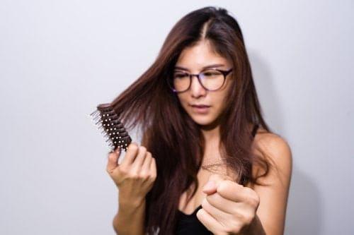 امرأة تمشط شعرها وشعرها بيدها.