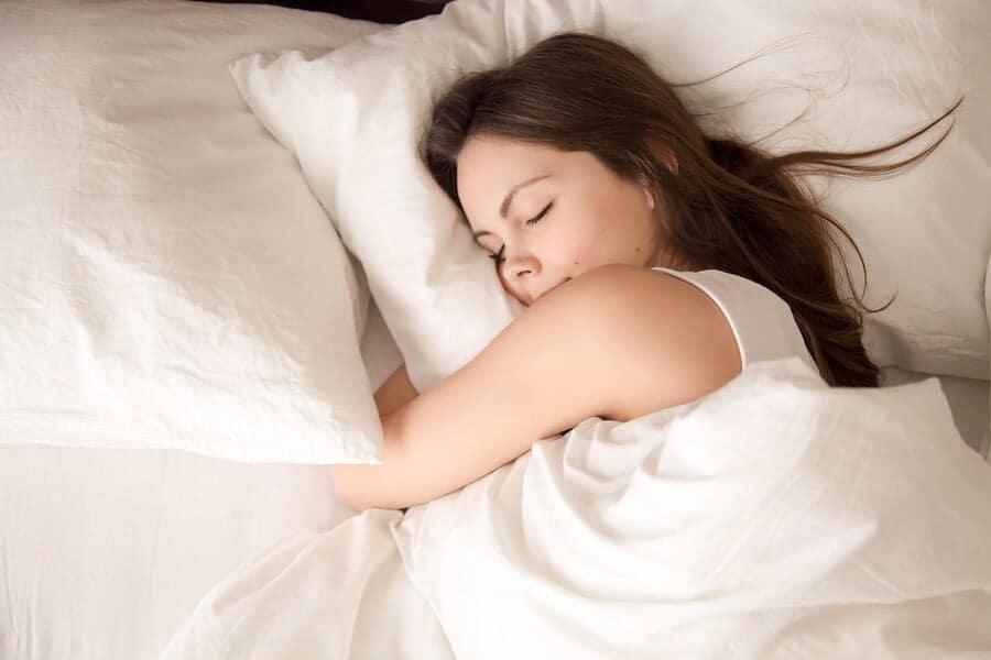 امرأة شابة تنام بهدوء وهي تعانق وسادة ناعمة.