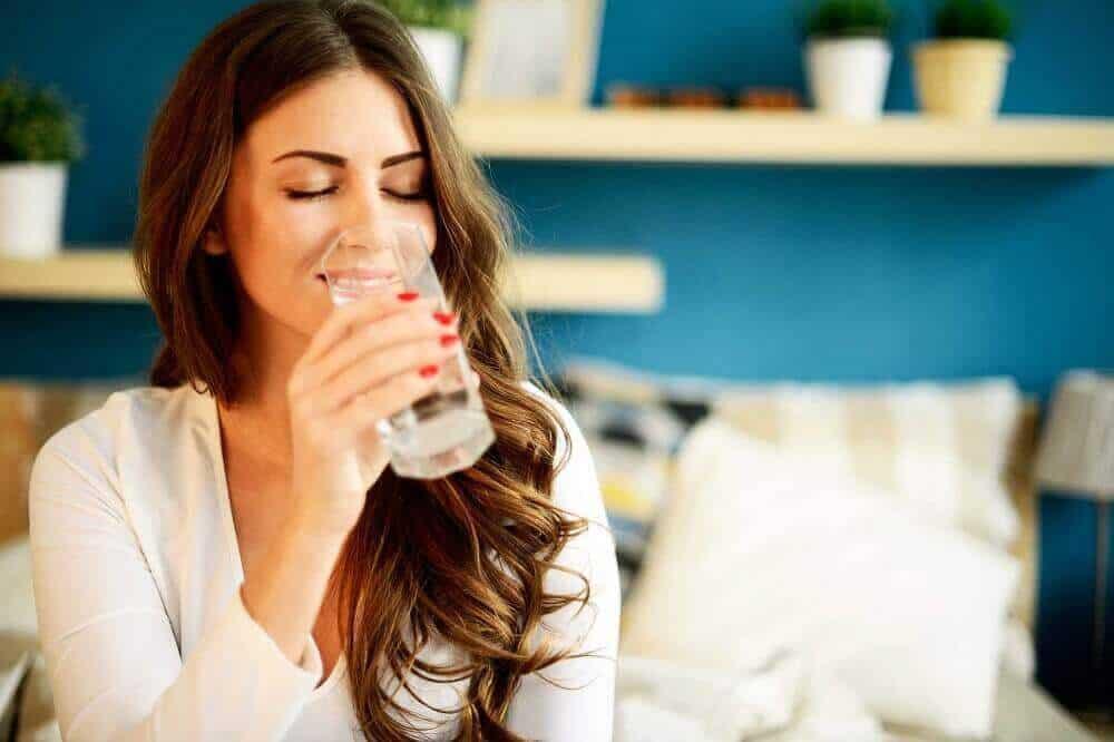 дівчина п'є воду в період менопаузи