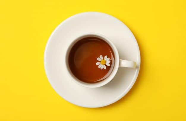 Premium Photo | Cup of chamomile tea on yellow background