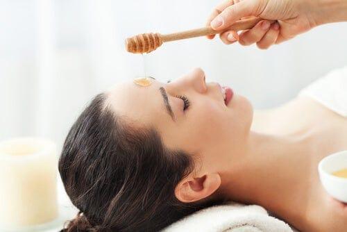 امرأة تعالج بالعسل على وجهها.