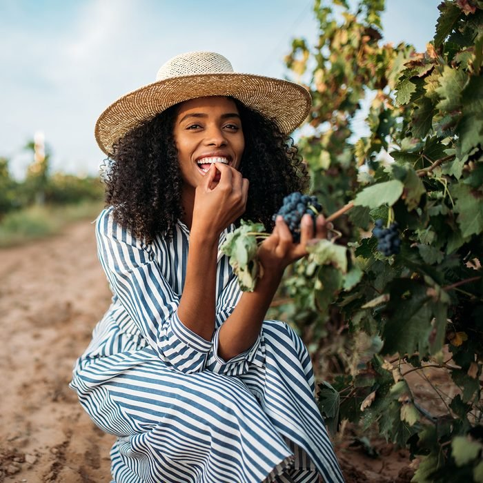 امرأة سوداء شابة تأكل عنب في كرم
